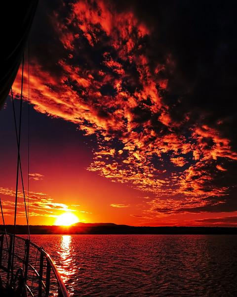 Red colored altocumulus cloud, sunset seascape.