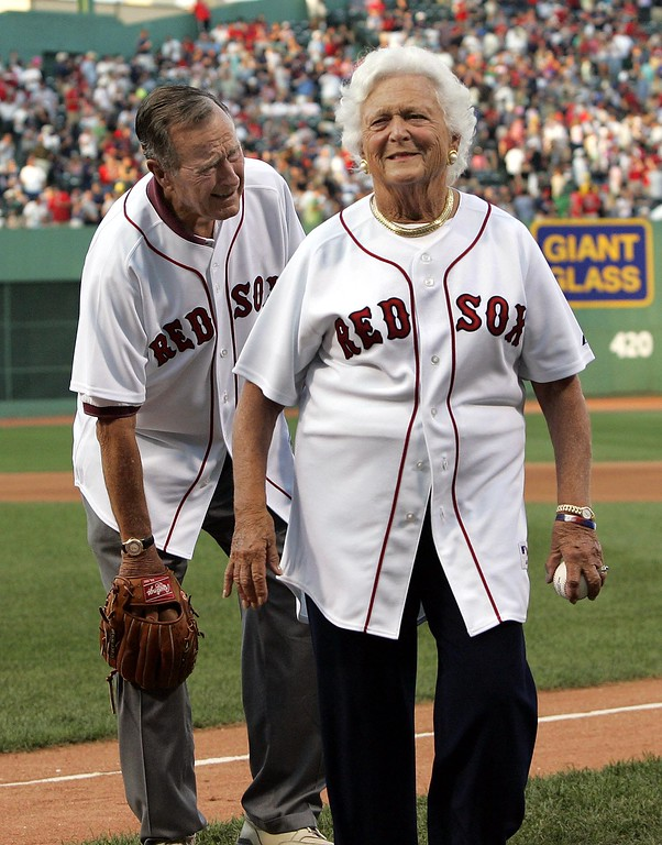 . Former President George Bush grimaces as he rubs his knee while he and former first lady Barbara Bush leave the field after she threw the ceremonial first pitch before the game between the Boston Red Sox and the Texas Rangers at Fenway Park in Boston Wednesday, Aug. 10, 2005. (AP Photo/Elise Amendola)