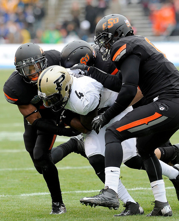 . From left, Oklahoma State cornerback Kevin Peterson, linebacker Alex Elkins and safety Daytawion Lowe tackle Purdue wide receiver O.J. Ross (4) in the first half of the Heart of Dallas Bowl NCAA college football game, Tuesday, Jan. 1, 2013,in Dallas. (AP Photo/Matt Strasen)