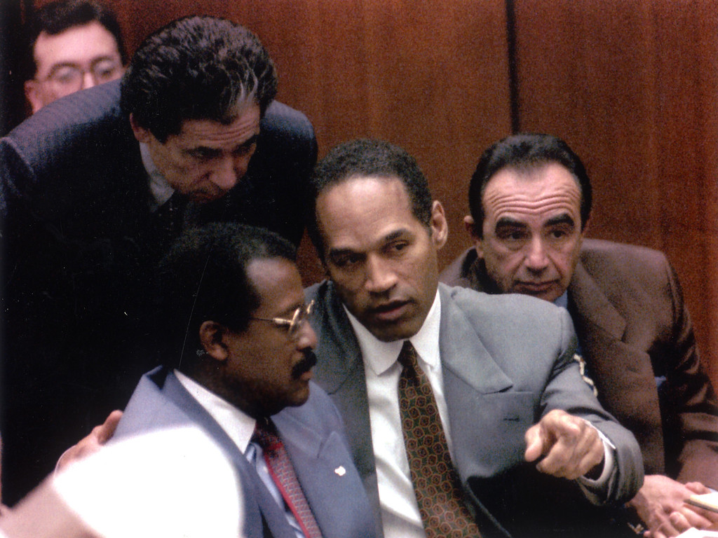 . O.J. Simpson confers with attorneys Robert Kardashian, standing, Johnnie Cochran Jr., and Robert Shapiro in court.   (1995) (Los Angeles Daily News file photo)