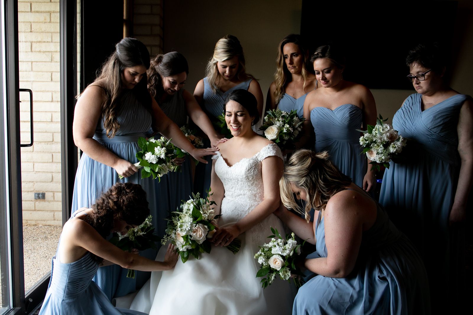 eight bridesmaids standing around the bride as they pray before her wedding