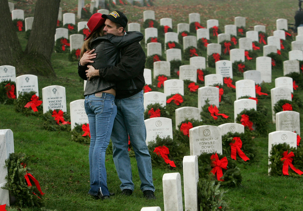 . Iraq war veteran Andy Schober, right, hugs his fiancee Leslie Morton, left,  during the annual holiday wreath laying, sponsored by The Arlington Wreath Project, part of the Wreaths Across America program, Thursday, Dec. 14, 2006 at Arlington National Cemetery in Arlington, Va.. (AP Photo/Evan Vucci)
