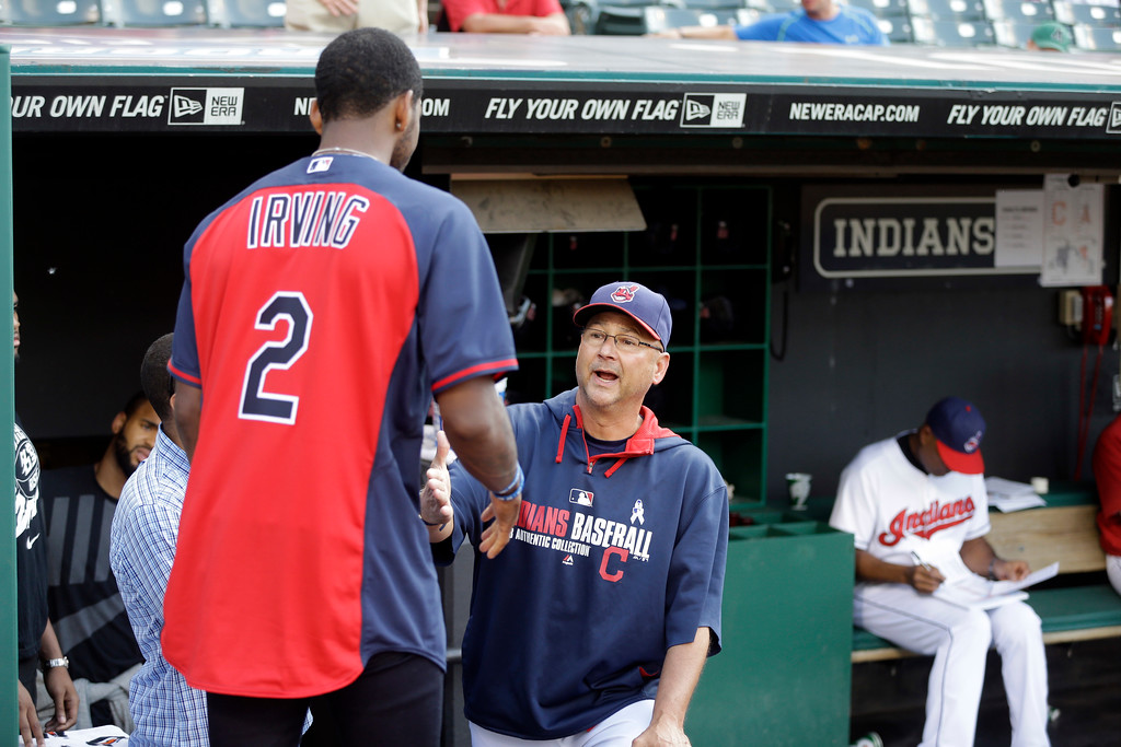 . Cleveland Indians manager Terry Francona shakes hands with Cleveland Cavalier guard Kyrie Irving (2) before a baseball game against the Los Angeles Angels Monday, June 16, 2014, in Cleveland. (AP Photo/Mark Duncan)