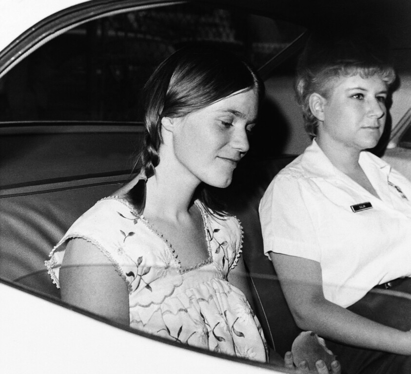. Linda Kasabian, left, the states principal witness in the murder trial of Charles Manson and three girl companions, is driven from the Los Angeles Hall of Justice in custody of the sheriffs matron after beginning her story of how actress Sharon Tate and six others were slain, Monday, July 28, 1970, Los Angeles, Calif. She resumes her testimony. (AP Photo)
