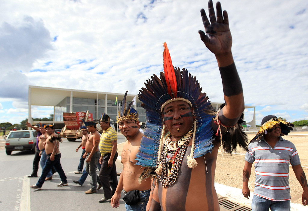 . A Brazilian Munduruku Indian raises his hand during a protest where they are prevented by security forces from entering the Planalto Palace, in Brasilia June 6, 2013. They are demonstrating against violations of indigenous rights and calling for the suspension of the construction of the Belo Monte hydroelectric plant on the Xingu river, a huge project aimed at feeding Brazil\'s fast-growing demand for electricity. REUTERS/Ueslei Marcelino