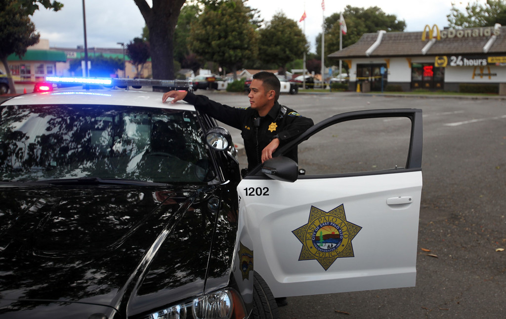 . Police officer Rolando Igno guards a crime scene where six people, including a 6-year-old child, were shot in broad daylight at a busy McDonald\'s restaurant on University Avenue in East Palo Alto, Calif., on Sunday, May 5, 2013. (Karl Mondon/Bay Area News Group)