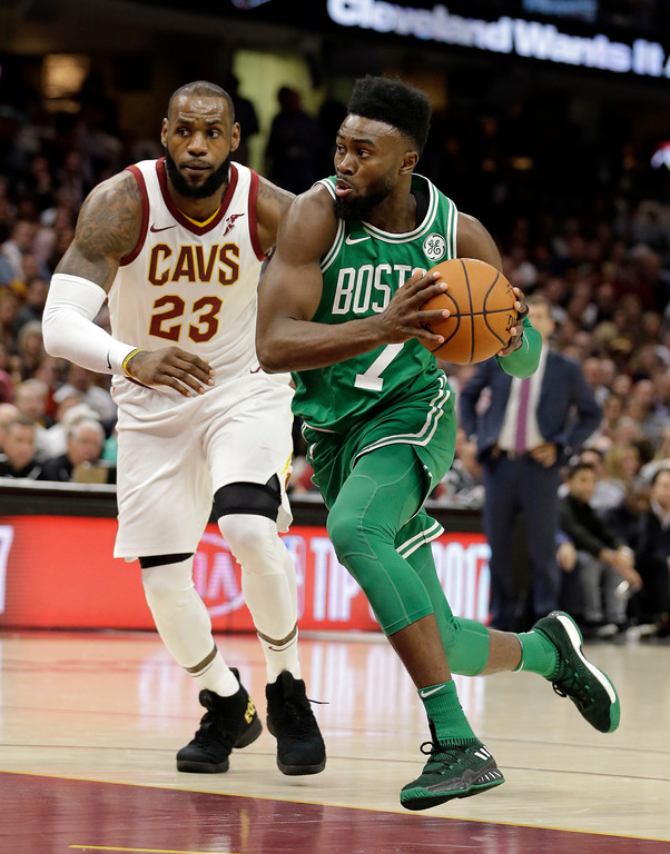 . Boston Celtics\' Jaylen Brown (7) drives past Cleveland Cavaliers\' LeBron James (23) in the first half of an NBA basketball game, Tuesday, Oct. 17, 2017, in Cleveland. (AP Photo/Tony Dejak)
