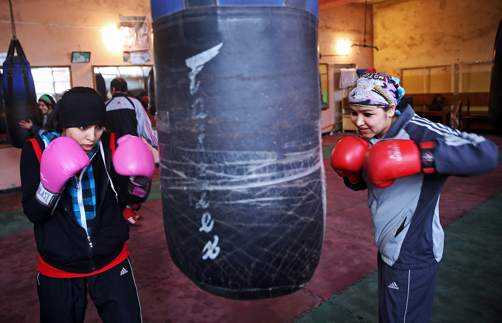 . In this Wednesday, March, 5, 2014 photo, Afghan women boxers practice at the Kabul stadium boxing club. A few yellow lamps light up the cavernous, sparsely furnished room where Afghanistanís young female boxers train, hoping to become good enough to compete in the 2016 Olympics. (AP Photo/Massoud Hossaini)