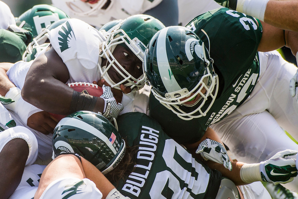 . Eastern Michigan running back Bronson Hill butts helmets with Michigan State linebacker Jon Reschke as he tries to dive over a pile of players for a failed first down during the first half on Saturday, Sept. 20, 2014 at Spartan Stadium in East Lansing, Mich. (AP Photo/The Flint Journal, Jake May)