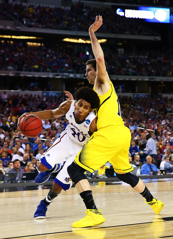 . ARLINGTON, TX - MARCH 29:  Kevin Young #40 of the Kansas Jayhawks drives against Glenn Robinson III #1 of the Michigan Wolverines in the first half during the South Regional Semifinal round of the 2013 NCAA Men\'s Basketball Tournament at Dallas Cowboys Stadium on March 29, 2013 in Arlington, Texas.  (Photo by Tom Pennington/Getty Images)