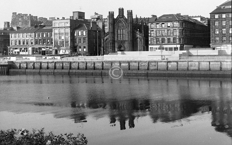 Clyde St from Carlton Place. St Andrew's has now had its face washed, and has gained some elbow room, some trees and some new neighbours. I don't think any of the other buildings in this shot are still there. The towering bulk top left was St Enoch Hotel / Station.    September 1973.