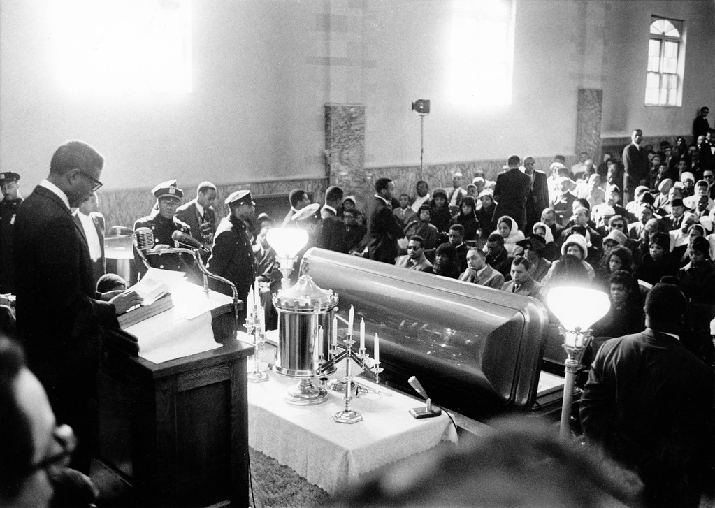 ". Actor Ossie Davis delivers eulosy for Malcolm X at the funeral services for the slain black Nationalist leader in the Faith Temple of God in Christ in New York\'s Harlem, February 27, 1965. Davis called Malcolm a ""Brave and gallant young champion.\"" Seated second from left in pew facing open casket is Malcolm\'s widow, Betty. (AP PHOTO)"