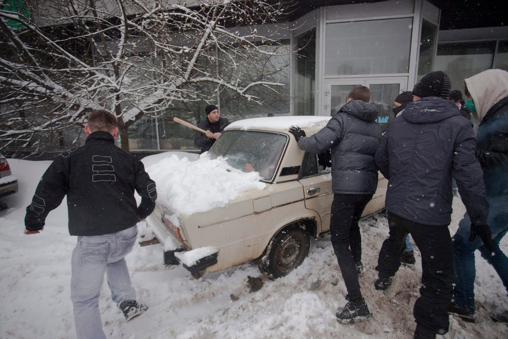 . In this photo taken on Friday, March 15, 2013, members of a pro-Kremlin youth group attack pushers of spice, a synthetic drug, one of which is swinging a bat at them in Moscow, Russia. Russian officials and anti-drugs campaigners say that spice has become one of the most dangerous drugs widely available to youngsters and almost impossible to ban because of the constantly changing chemical ingredients. (AP Photo/Alexander Zemlianichenko Jr)