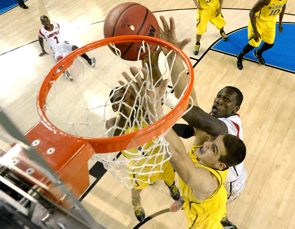 . Michigan Wolverines forward Glenn Robinson III (lower) reaches for a rebound against Louisville Cardinals center Gorgui Dieng (top) in the first half of their NCAA men\'s Final Four championship basketball game in Atlanta, Georgia April 8, 2013. REUTERS/Chris Steppig-Pool