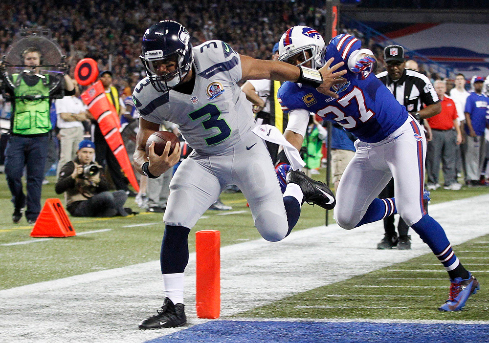 . Seattle Seahawks\' Russell Wilson (L) scores a touchdown against Buffalo Bills\' Khari Brown during the first half of their NFL football game in Toronto, December 16, 2012. REUTERS/Mark Blinch