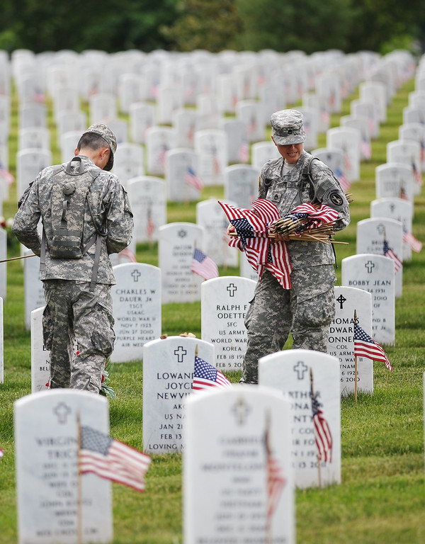 . Members of the Third US Infantry Regiment, The Old Guard, place flags in front of graves at Arlington National Cemetery on May 23, 2013 in Arlington, Virginia ahead of Memorial Day.  AFP PHOTO/Mandel NGAN/AFP/Getty Images
