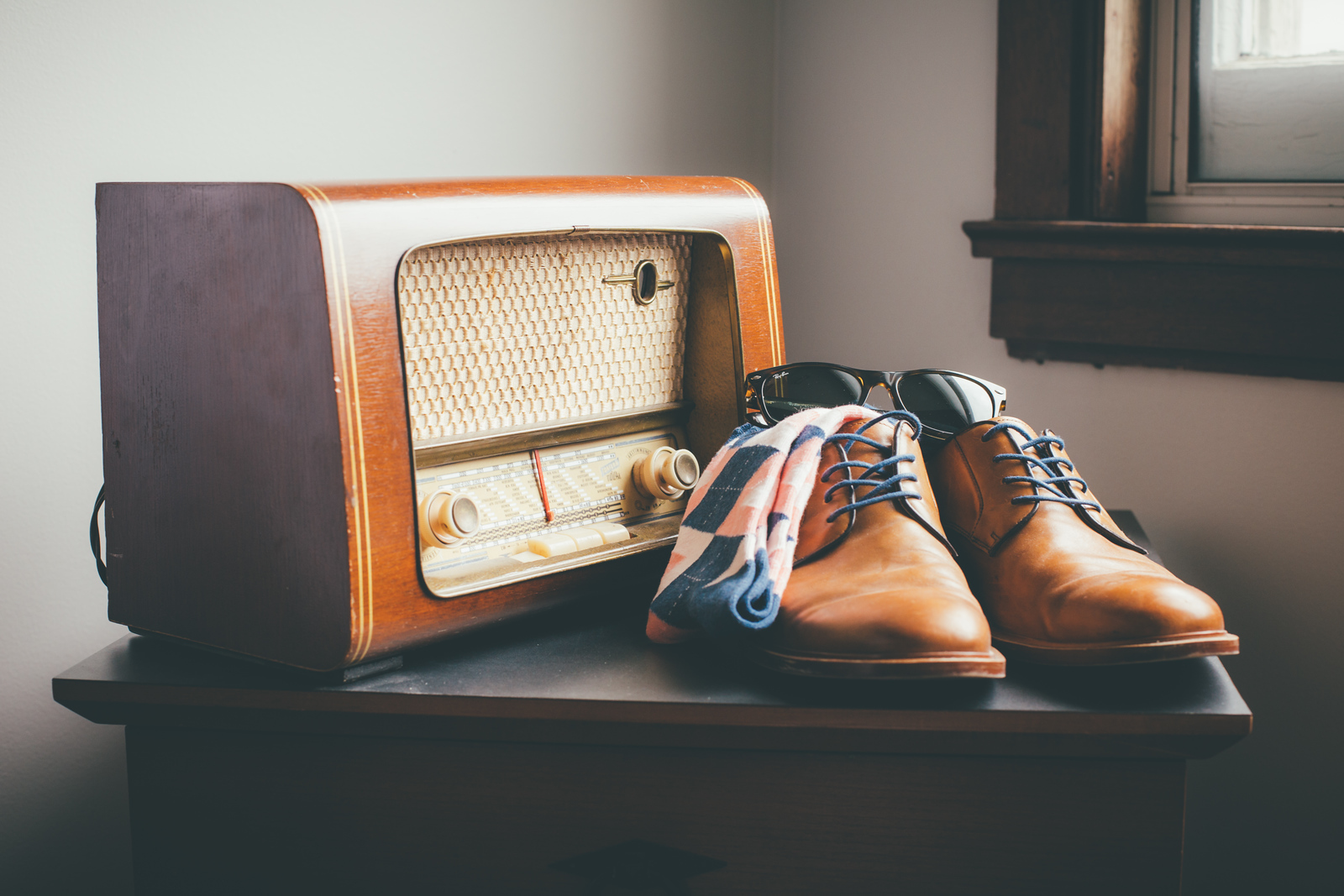 a groom's wedding shoes and socks sitting on an end table next to an antique turn dial tube radio with sunglasses perched on top