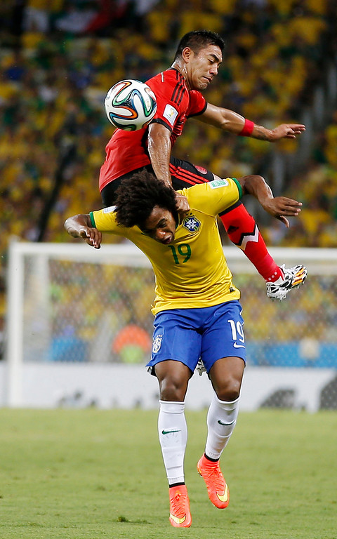 . Mexico\'s Marco Fabian flips over Brazil\'s Willian while trying to head the ball during the group A World Cup soccer match between Brazil and Mexico at the Arena Castelao in Fortaleza, Brazil, Tuesday, June 17, 2014.  (AP Photo/Eduardo Verdugo)