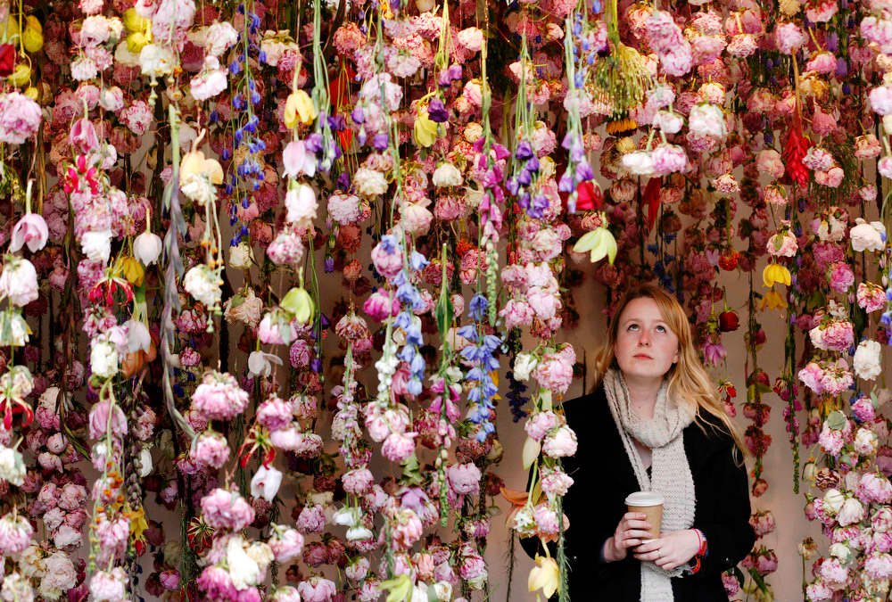 . A woman walks through floral artist Rebecca Louise Law\'s stand at the Chelsea Flower Show in London May 21, 2013. REUTERS/Luke MacGregor