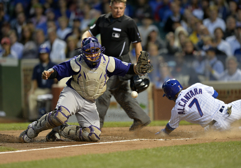 . Arismendy Alcantara #7 of the Chicago Cubs scores past catcher Wilin Rosario #20 of the Colorado Rockies on a sacrifice fly by Justin Ruggiano during the fourth inning on July 28, 2014 at Wrigley Field in Chicago, Illinois.  (Photo by Brian Kersey/Getty Images)