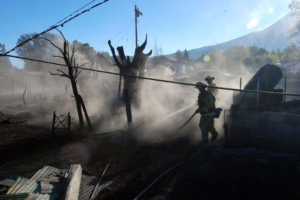 . Firefighters hose down the smoldering remains of a home, Tuesday, Sept. 16, 2014, in Weed, Calif. A fast-moving wildfire destroyed at least 100 structures before winds died down and firefighters got a line around most of the fire. (AP Photo/Jeff Barnard)
