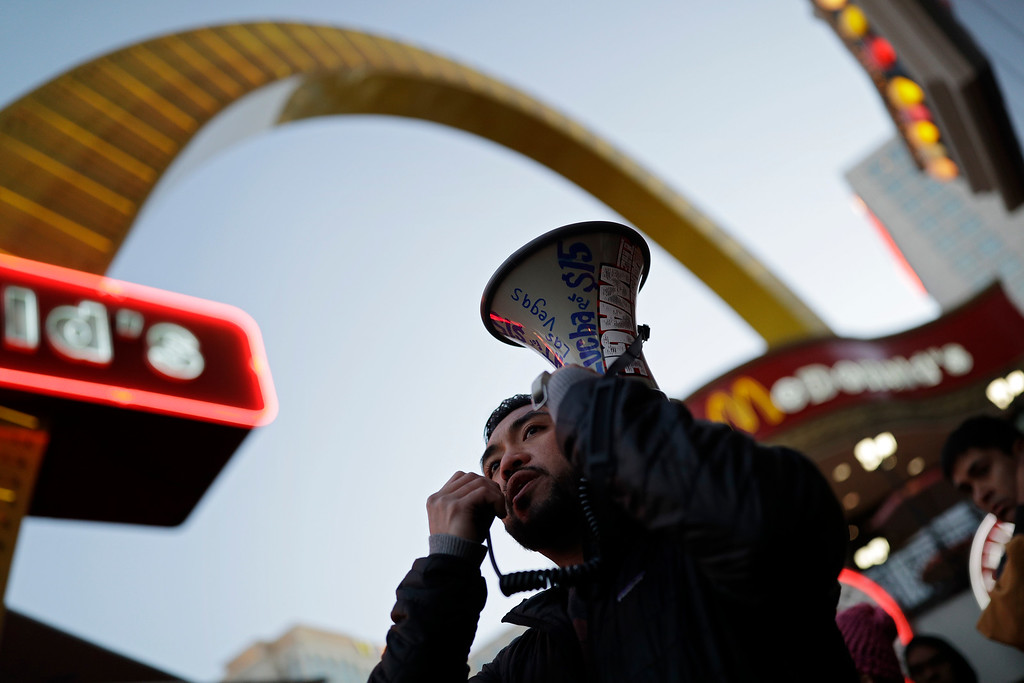 . A.J. Buhay speaks on a bullhorn as he and others protest near a McDonald\'s restaurant along the Las Vegas Strip, Tuesday, Nov. 29, 2016, in Las Vegas. The protest was part of the National Day of Action to Fight for $15. The campaign seeks higher hourly wages, including for workers at fast-food restaurants and airports. (AP Photo/John Locher)
