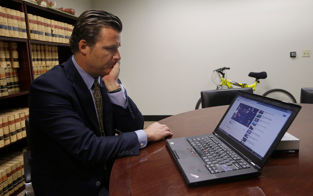 . Robert Allard, an attorney for the family of Audrie Pott, watches a video of Pott at his office in San Jose, Calif., Friday, April 12, 2013. Allard said that Pott committed suicide after she was sexually assaulted by three of her friends and a photo surfaced online. (AP Photo/Jeff Chiu)