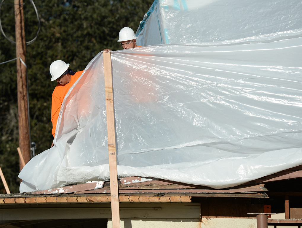 . Workers put up tarps as Asbestos is being removed by Resource Environmental, Inc. from La Habra Heights City Hall on Wednesday January 22, 2014. More asbestos was found in the roofing material last week. (Staff Photo by Keith Durflinger/Pasadena Star-News)