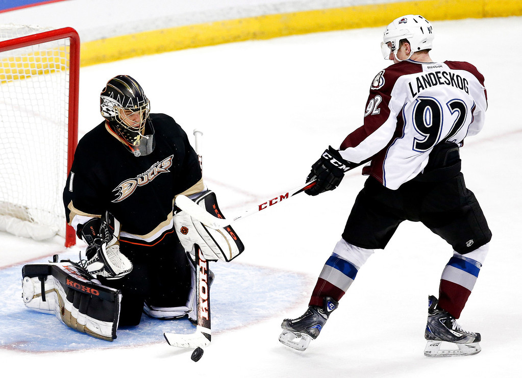 . Anaheim Ducks goalie Jonas Hiller, left, blocks a shot by Colorado Avalanche left wing Gabriel Landeskog during overtime of an NHL hockey game in Anaheim, Calif., Sunday, Feb. 24, 2013. The Ducks won 4-3. (AP Photo/Chris Carlson)