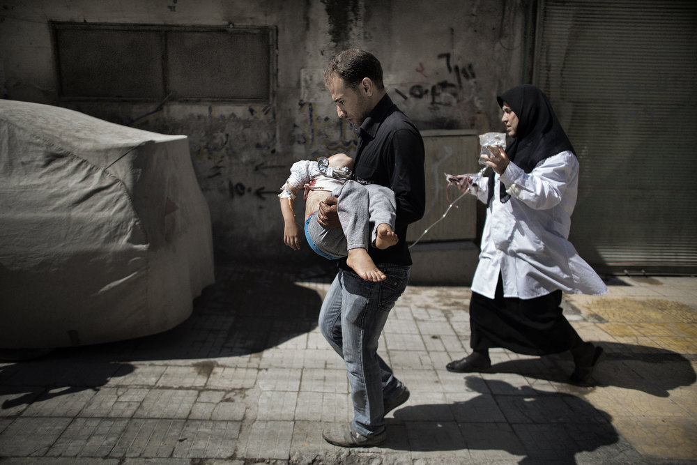 Description of . A Syrian man carries his wounded daughter outside a hospital in the northern city of Aleppo on September 18, 2012. Syrian troops shelled several districts in Aleppo and clashed with rebels, as Damascus ally Iran proposed a simultaneous halt to the violence and a peaceful solution to the conflict. MARCO LONGARI/AFP/Getty Images