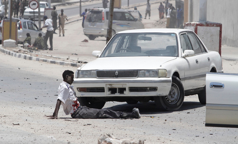 . An unidentified man who is injured in an explosion sits on the road near the presidential palace in Mogadishu March 18, 2013. A car bomb exploded near the presidential palace in the Somali capital Mogadishu on Monday, killing at least 10 people in a blast that appeared to target senior government officials, police said. REUTERS/Feisal Omar