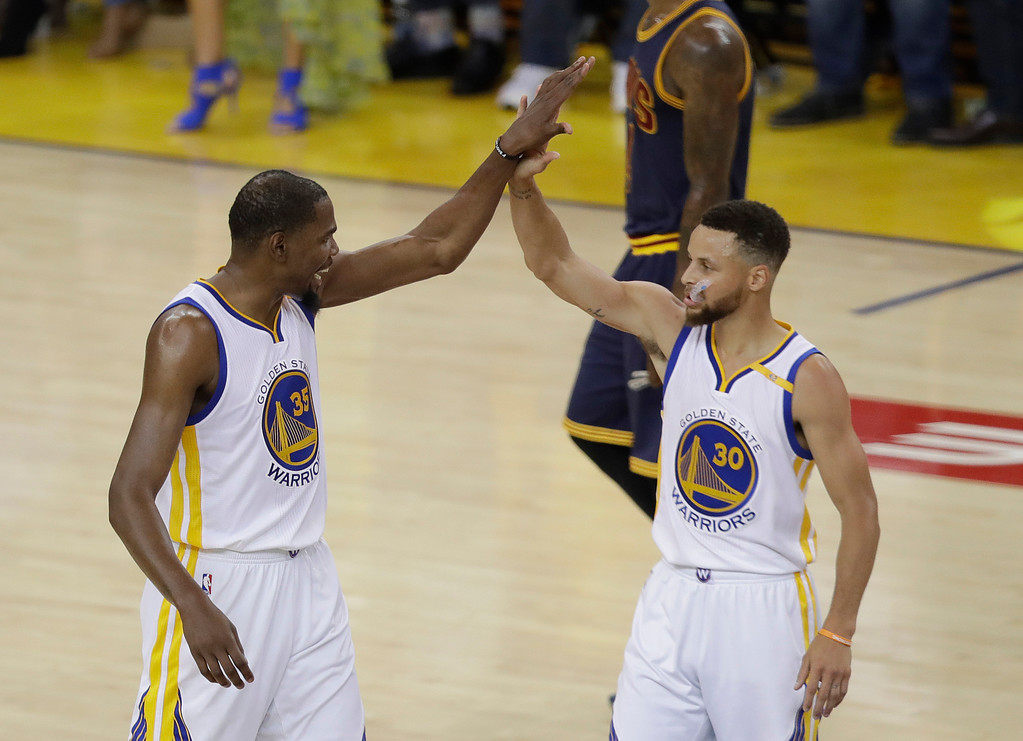 . Golden State Warriors forward Kevin Durant (35) and guard Stephen Curry (30) react during the first half of Game 1 of basketball\'s NBA Finals against the Cleveland Cavaliers in Oakland, Calif., Thursday, June 1, 2017. (AP Photo/Marcio Jose Sanchez)