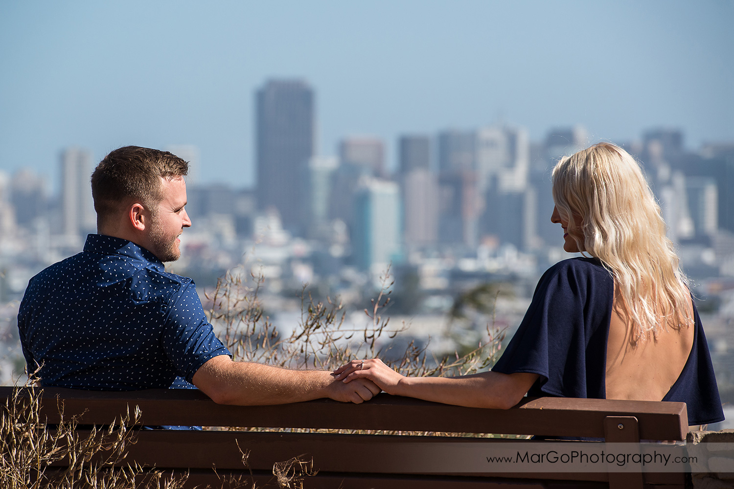 engagement session at Bernal Heights in San Francisco - cupule holding hands with SF view