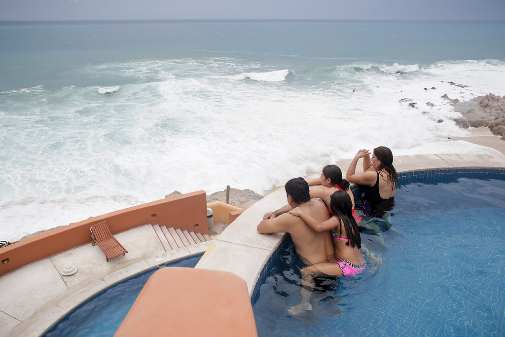 . Tourists watch the ocean from inside a swimming pool at a resort in Los Cabos, Mexico,  Sunday, Sept. 14, 2014. Hurricane Odile turned into a Category 4 hurricane and it\'s expected to make a close brush with the southern portion of Mexico\'s Baja California peninsula Sunday evening. (AP Photo/Victor R. Caivano)