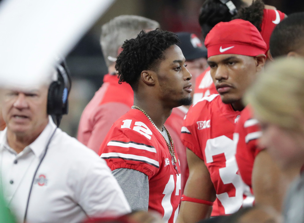 . Ohio State cornerback Denzel Ward (12) watches from the sidelines during the first half of the Cotton Bowl NCAA college football game against the Southern California in Arlington, Texas, Friday, Dec. 29, 2017. (AP Photo/LM Otero)