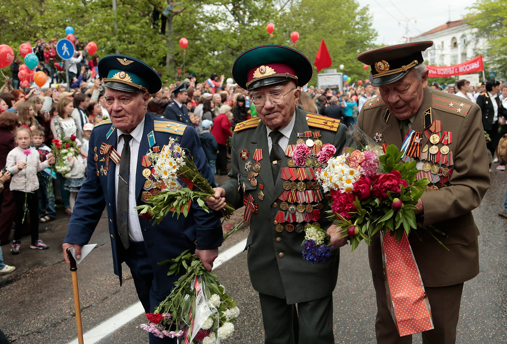 . WWII veterans walk during a Victory Day military parade in Sevastopol, Crimea, Friday, May 9, 2014. Crimea, which hosts a major Russian Black Sea Fleet base, is also set to hold a massive navy parade in the port of Sevastopol, celebrating the Russian takeover. (AP Photo/Ivan Sekretarev)