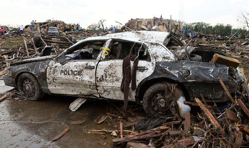 . A damaged police car is seen after a tornado struck Moore, Oklahoma, May 20, 2013. A 2-mile-wide (3-km-wide) tornado tore through the Oklahoma City suburb of Moore on Monday, killing at least 51 people while destroying entire tracts of homes, piling cars atop one another, and trapping two dozen school children beneath rubble. REUTERS/Gene Blevins