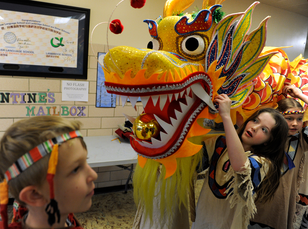 . Preparing to lead the performance, fourth-grader Paris Nissen, 9, center, is the head of the dragon and classmate Matthew Medvedskiy, left, will tempt the dragon with a bright, shiny ball. Students at the Denver Language School ring in the Year of the Snake with their Chinese New Year celebration performance in the school auditorium. Kindergarteners through 4th grade perform traditional dances dressed in colorful Chinese costumes. According to the school principal, Chinese New Year is the most important of the traditional Chinese holidays. Families make way for  good luck by cleaning their homes symbolizing reconciliation and forgetting old grudges in exchange for peace and happiness. The Chinese New Year (Feb. 10) follows the Chinese 12 Zodiac Calendar Year designating 2013 the Year of the Snake. (Photo By Kathryn Scott Osler/The Denver Post)