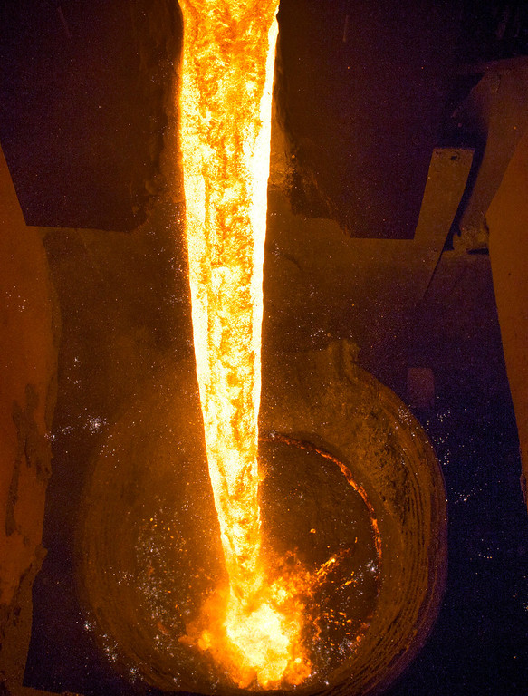 . Molten metal pours from the blast furnace into a waiting cauldron inside the Zaporizhstal steel plant, owned and operated by Metinvest BV, at their site in Zaporizhzhya, Ukraine, on Monday, Oct. 14, 2013. Metinvest BV, Ukraine\'s largest steelmaker, last year acquired 49.9% in steelmaker Zaporizhstal a manufacturer of semi-finished steel products, including hot and cold-rolled plates and coils. Photographer: Vincent Mundy/Bloomberg