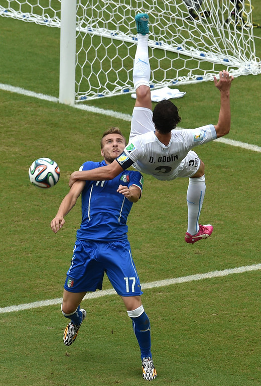 . Uruguay\'s defender Diego Godin (R) kicks the ball past Italy\'s forward Ciro Immobile during a Group D football match between Italy and Uruguay at the Dunas Arena in Natal during the 2014 FIFA World Cup on June 24, 2014.  YASUYOSHI CHIBA/AFP/Getty Images