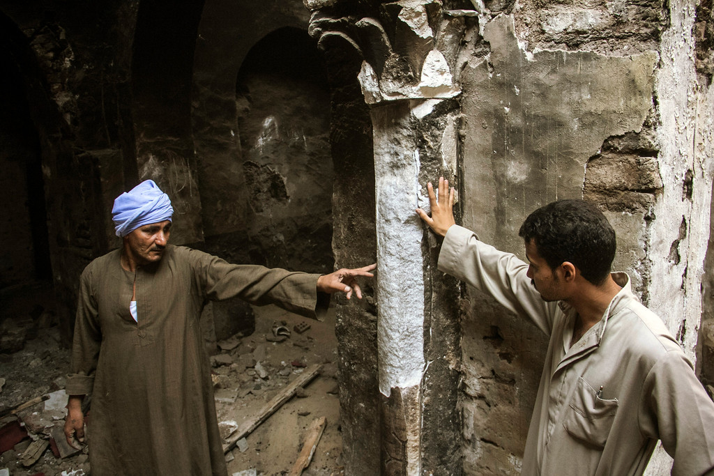 . In this Sept. 3, 2013 photo, Egyptian Christian villagers point out a damaged column that they claim drips water every Good Friday at the damaged ancient chapel inside the Virgin Mary and St. Abraam Monastery that was looted and burned by Islamists in Dalga, Minya province, Egypt. Dalga has been outside government control since hard-line supporters of the Islamist Mohammed Morsi drove out police and occupied their station on July 3, the day Egypt\'s military chief removed the president in a popularly supported coup. It was part of a wave of attacks in the southern Minya province that targeted Christians, their homes and businesses. (AP Photo/El Shorouk Newspaper, Roger Anis)