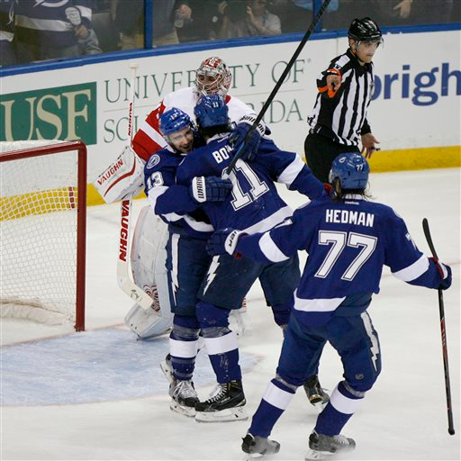 . Tampa Bay Lightning\'s Cedric Paquette (13), Brian Boyle (11) and Victor Hedman (77) gather to celebrate Boyle\'s first-period goal against Detroit Red Wings goalie Petr Mrazek (34) during Game 1 of an NHL hockey first-round playoff series, Thursday, April 16, 2015, in Tampa, Fla. (Douglas R. Clifford/Tampa Bay Times via AP)