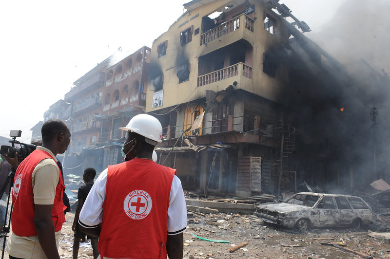 . Red Cross officials walk look at a building on fire after a heavy explosion on December 26, 2012 in Lagos. Fire ripped through a crowded neighborhood in Nigeria\'s largest city and wounded at least 30 people after a huge explosion rocked a building believed to be storing fireworks, officials said.  Fireworks continued to explode well after the fire began while smoke was heavy and the blaze intense, making it difficult for rescue workers and firefighters to approach the scene. AFP PHOTO/PIUS  UTOMI EKPEI/AFP/Getty Images