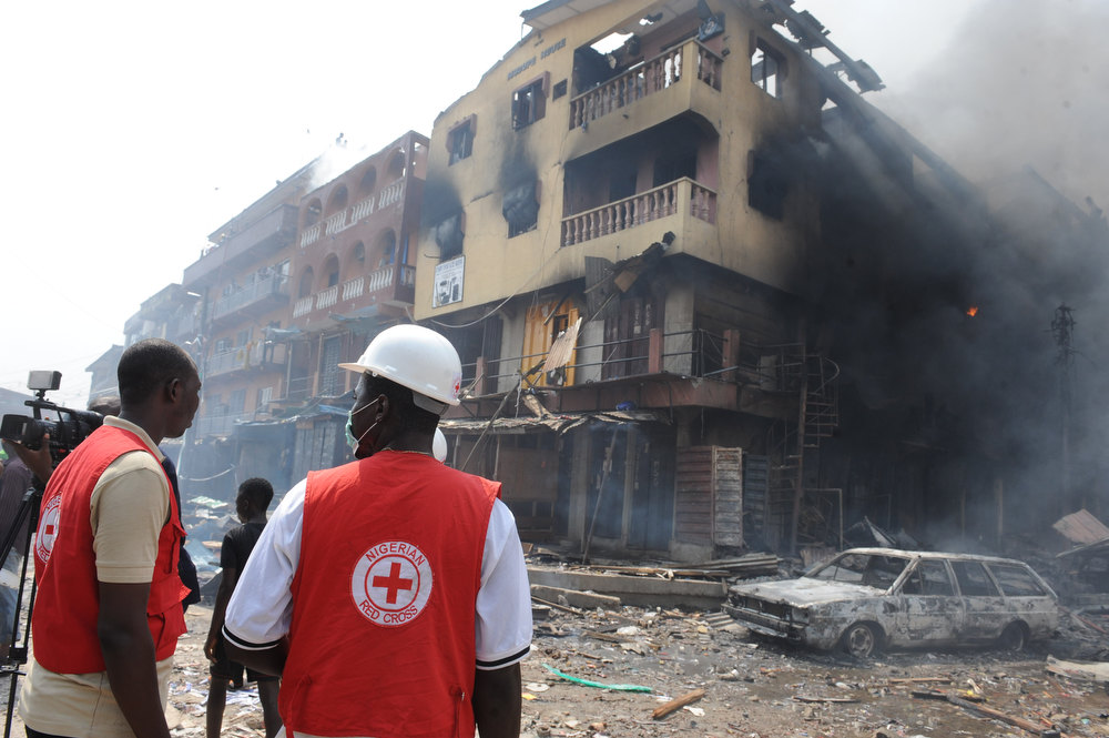 Description of . Red Cross officials walk look at a building on fire after a heavy explosion on December 26, 2012 in Lagos. Fire ripped through a crowded neighborhood in Nigeria\'s largest city and wounded at least 30 people after a huge explosion rocked a building believed to be storing fireworks, officials said.  Fireworks continued to explode well after the fire began while smoke was heavy and the blaze intense, making it difficult for rescue workers and firefighters to approach the scene. AFP PHOTO/PIUS  UTOMI EKPEI/AFP/Getty Images