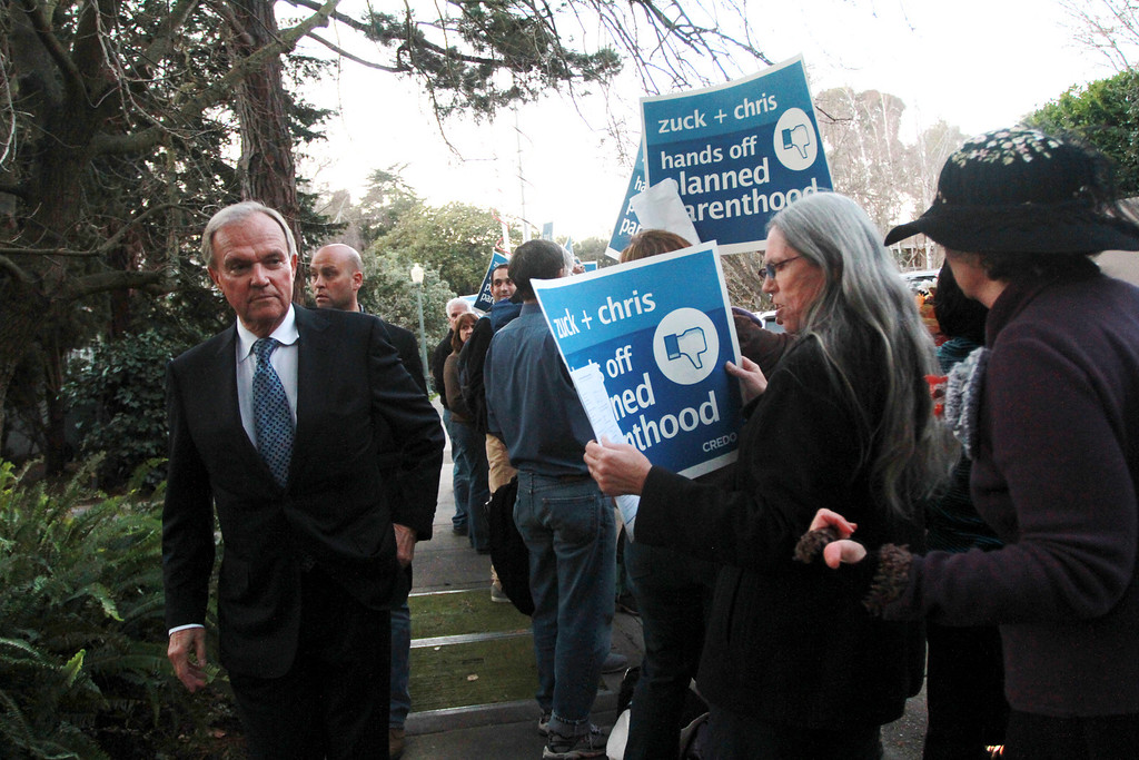 ". A guest to a campaign fundraiser for New Jersey Republican Gov. Chris Christie walks past protesters standing in front of the home of Facebook CEO Mark Zukerberg in Palo Alto on Wednesday, Feb. 13, 2013. About 40 protesters rallied in front of the home, saying they objected to Christie�s visit because of his efforts to strip funding from Planned Parenthood and other women�s reproductive health care programs. Protester and Palo Alto resident Cheryl Lilienstein said she wondered whether Zuckerberg had any idea what Planned Parenthood means for women\'s health or what Christie�s stances are. ""I hope he\'s just confused,\"" she said. Zuckerberg and wife Priscilla Chan first got to know Christie after donating $100 million to struggling Newark, N.J., schools two years ago, according to a Facebook spokeswoman.   (Kirstina Sangsahachart/ Daily News)"
