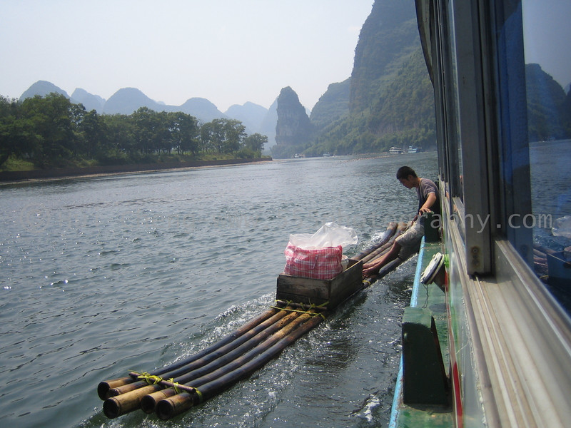 Jade seller resting against the tour boat.  Guilin, China