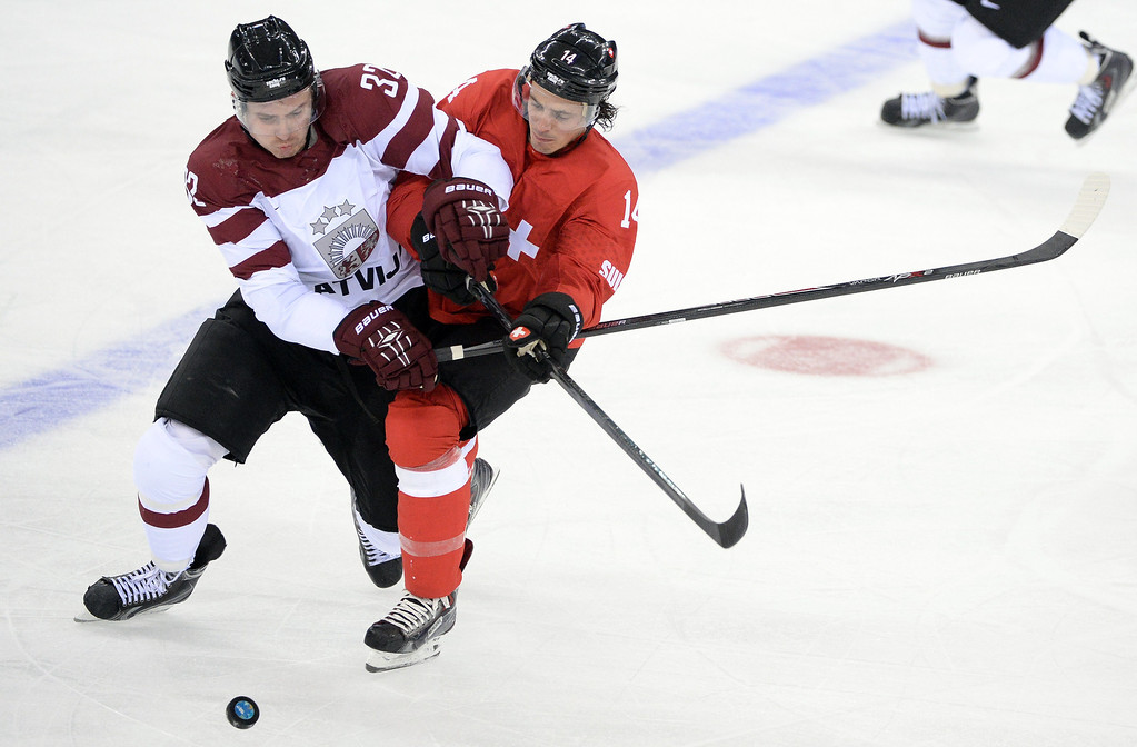 . Latvia\'s Arturs Kulda (L) vies for the puck with Switzerland\'s Roman Wick during the Men\'s Ice Hockey Group C match between Latvia and Switzerland at the Sochi Winter Olympics on February 12, 2014 at the Shayba Arena. ANDREJ ISAKOVIC/AFP/Getty Images