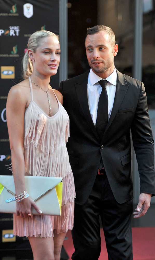 Description of . This picture taken on November 4, 2012 during the Feather Awards held at Melrose Arch in Johannesburg shows South Africa's Olympic sprint star Oscar Pistorius and his model girlfriend Reeva Steenkamp. Pistorius has been charged with the Valentine's Day murder of Steenkamp, police confirmed on February 14, 2013 ahead of his expected court appearance. South African police played down reports that Pistorius shot dead his girlfriend thinking she was an intruder, saying they had dealt with domestic incidents at his residence and will oppose bail.  LUCKY NXUMALO/AFP/Getty Images