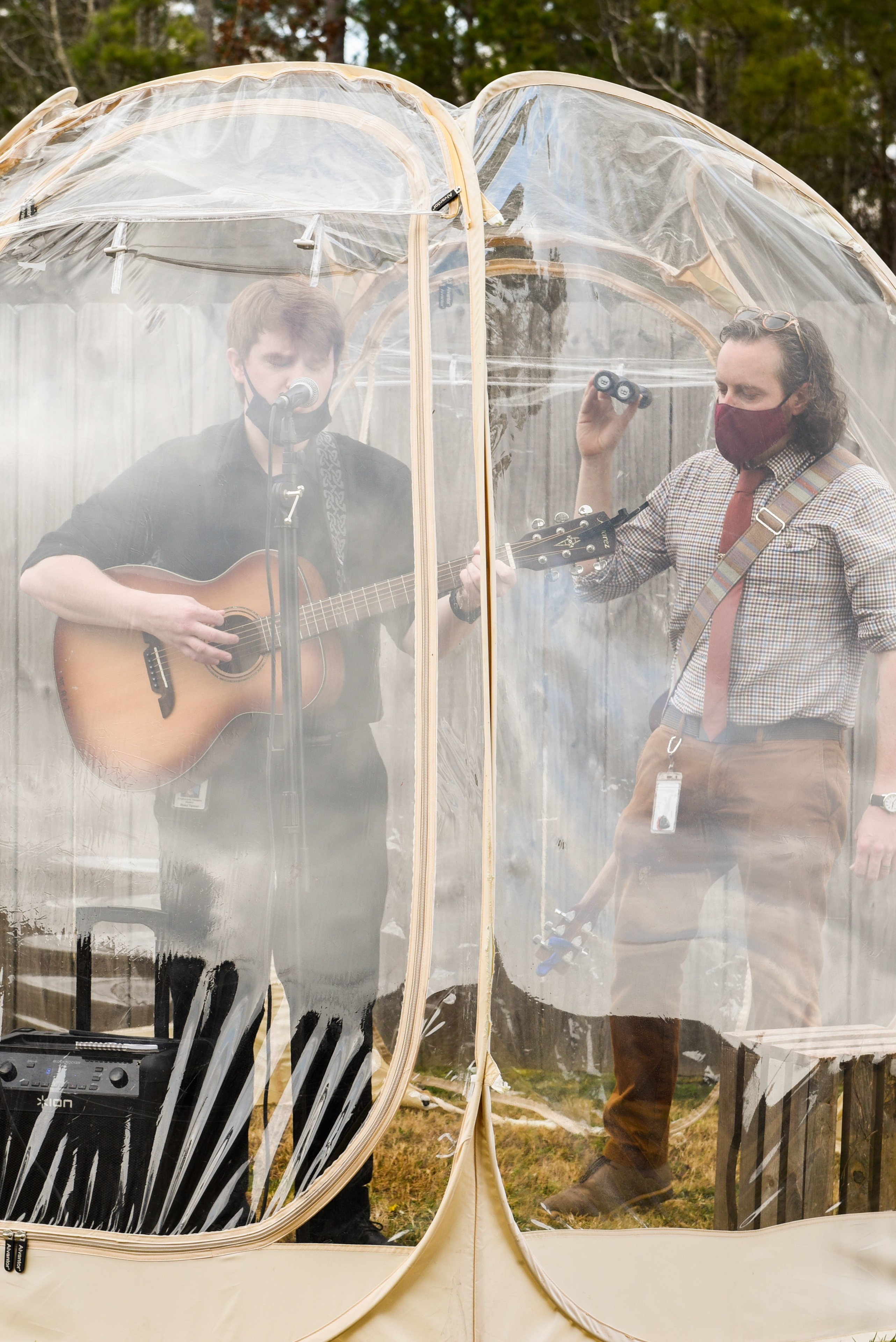 Senior Reed Tanner sings to elderly residents from inside a protective bubble, while graduate student Matthew Seymour backs him up with shaker sound.