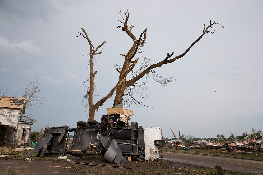 . A camper trailer is wrapped around a tree in Pilger, Neb.,  following a tornado on Monday, June 16, 2014.  The National Weather Service says the storm that struck northeast Nebraska appears to have produced four tornadoes, one of which ravaged the town of Pilger.   (AP Photo/The World-Herald, Ryan Soderlin)